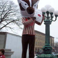 "Person in a Bucky Badger costume with a sign that reads ""Bucky supports the TAA and all unions"""